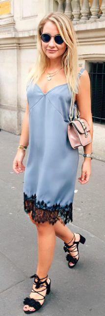 Look com vestido azul claro com detalhes de renda preta, bolsa de ombro em tom rosê e sandália preta de amarração.