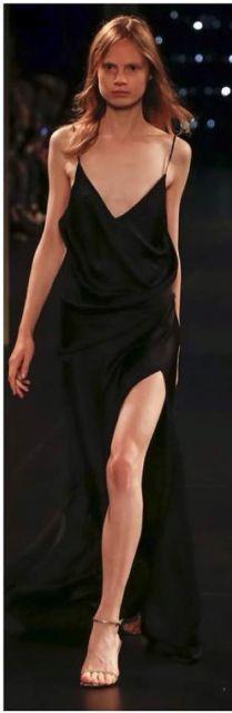 Modelo de vestido preto lingo com alcinhas finas e sandália dourada.