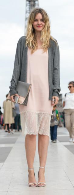 Modelo usa vestido rosê com renda no mesmo tom, sandália prata com bolsa de mão e caquinho no mesmo tom.