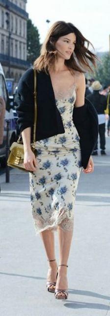 Loos com vestido estampa floral branco com azul, sandália, bolsa verde e casaco preto.