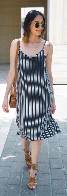 Modelo usa vestido de alcinha largo, estampado com risca de giz, bolsa e sapato em tons terra.