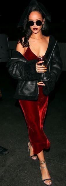 Rihanna veste vestido vermelho de veludo, com jaqueta de coro preta e sandália na mesma cor.