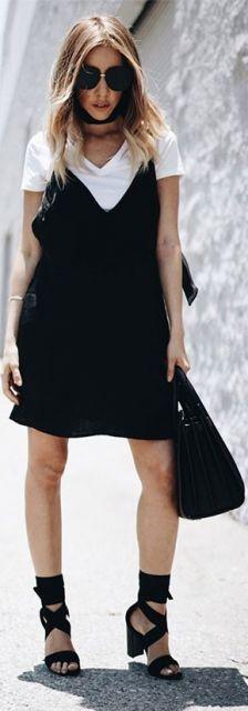 Modelo veste vestido preto com camiseta branca e sandália preta com bolsa na mesma cor.