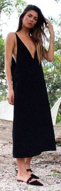 Modelo veste vestido slip dress preto comprido, com chinelo preto de bico.