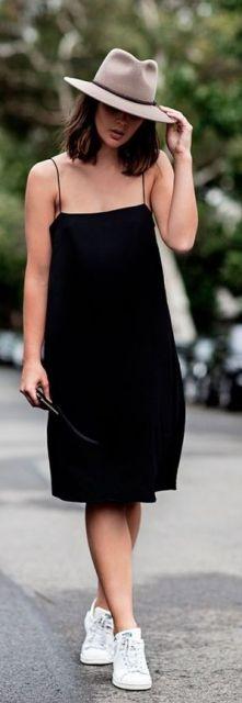 Modelo veste vestido preto de alcinhas finas com tênis branco e chapéu.