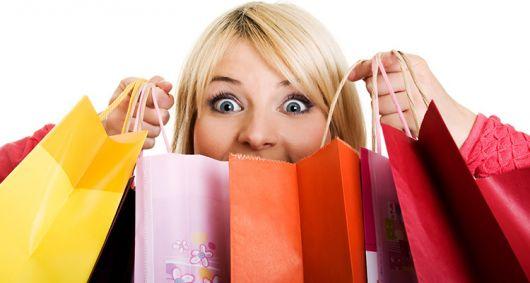 Mulher loira com várias sacolas de compras.
