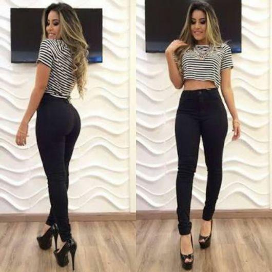 Modelo usa calça preta cintura alta, blusa listrada e sapato preto.