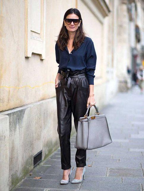 Modelo veste calça de couro larguinha, blusa azul larguinha e sapato cinza de bico.