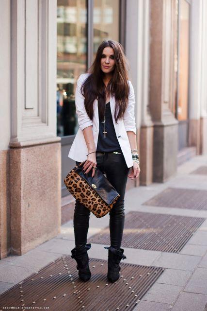 Modelo veste calça preta de couro, blusa preta e sneaker no mesmo tom.