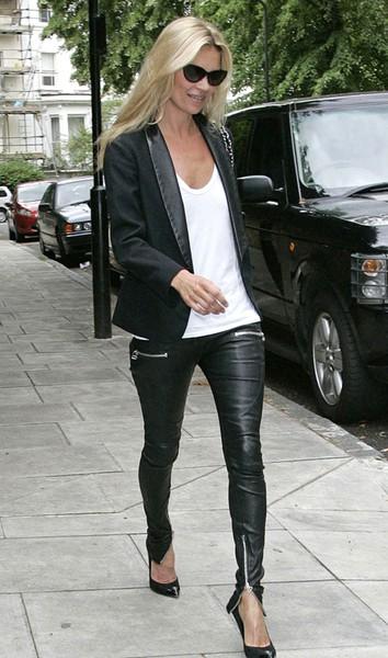 Modelo veste calça de couro preta, blusa branca e blazer preto.