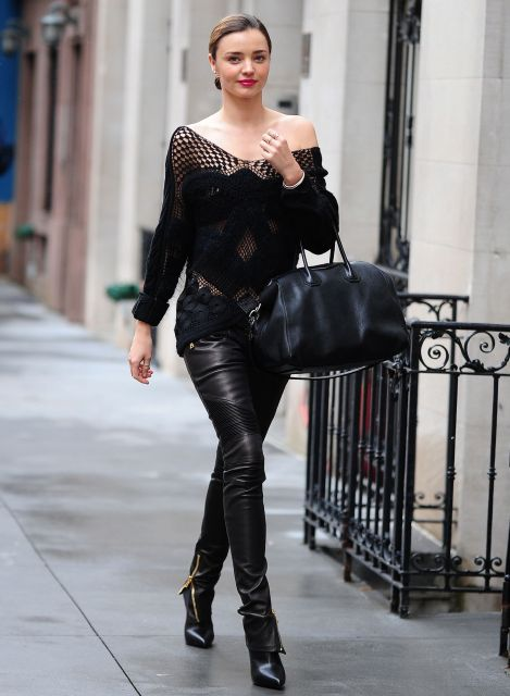 Modelo vesste calça de couro preta, blusa de tricot com transparências, bota no mesmo tom e bolsa.