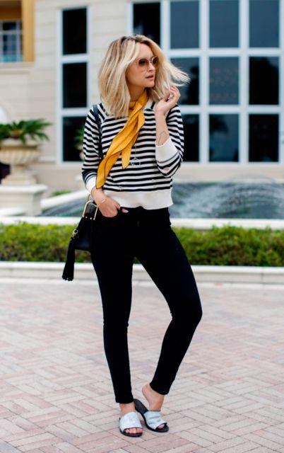 Modelo veste blusinha listrada, lenço amarelo, calça preta, chinelo slide e bolsa preta.