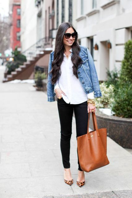Modelo veste calça preta jeans, blusa branca, jaqueta jeans e bolsa couro tons terrosos.