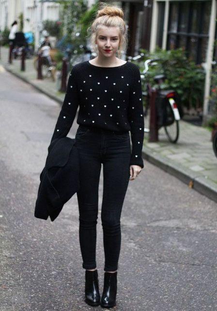 Modelo veste calça preta, blusa no mesmo tom com detalhes de bolinhas brancas.