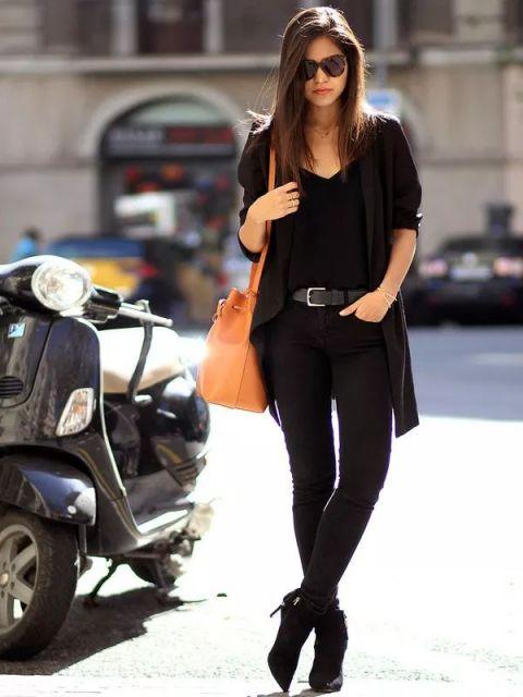 Modelo usa blusa, casaquinho, calça e bota preta com bolsa laranja.