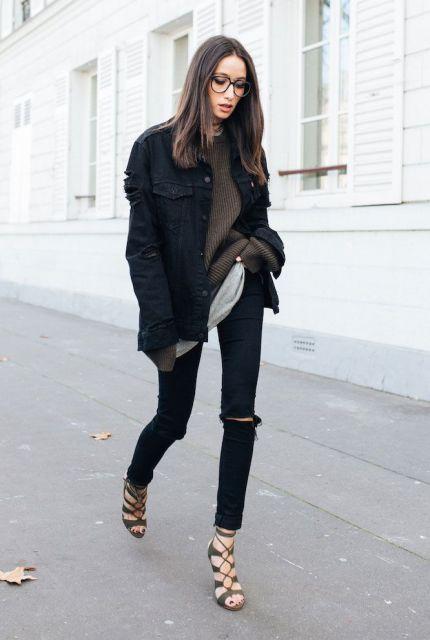 Modelo veste calça preta com rasgo no joelho, sandalia de amrraçoes, blusa marrom e jaqueta preta.