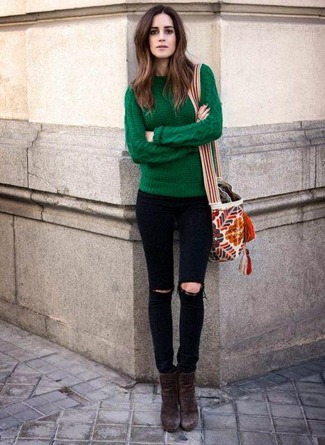 Modelo usa blusa verde, calça com rasgo no joelho e botinha marrom.