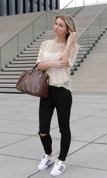 Modelo veste tênis branco e preto, bolsa marrom, blusa gelo e calça preta.