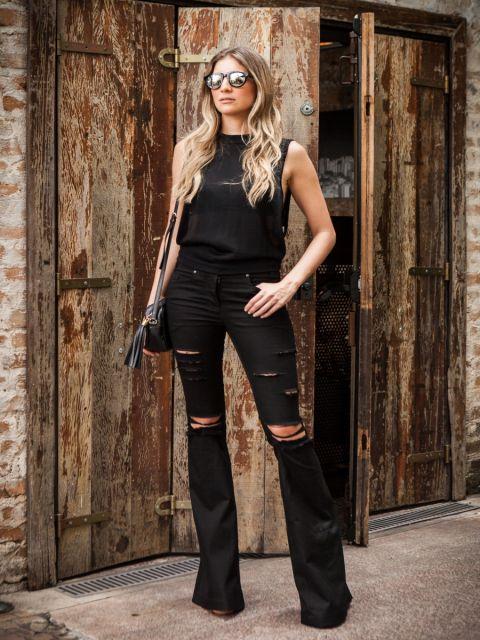 Modelo usa calça boca larga com rasgos em tom de preto, blusa , bolsa e sapato no mesmo tom.