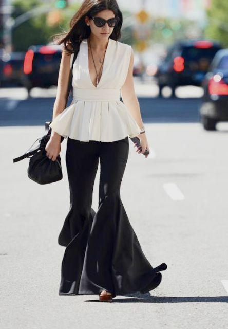 Modelo veste calça preta flare com blusa branco gelo e bolsa de ombro.