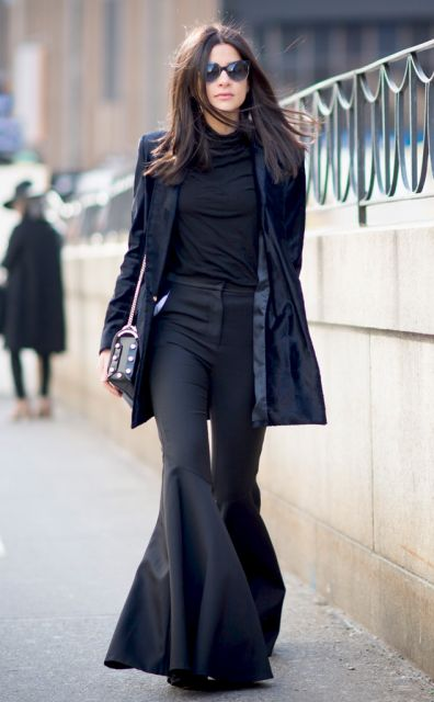 Modelo usa calça preta flare e blusa de gola preta e jaqueta azul escuro .