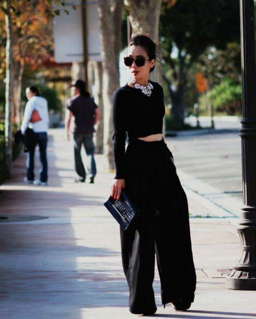 Modelo veste calça pantalona e blusa cropped manga longa preto com colar de brilhantes.