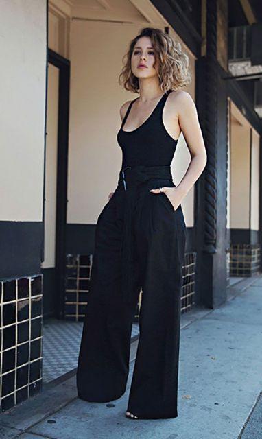 Modelo usa calça preta pantalona, e blusa preta de alcinha.