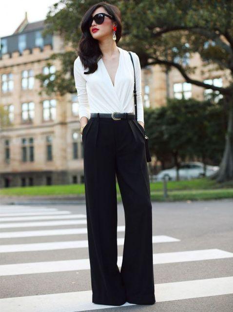 Modelo veste calça preta pantalona e blusa branca manga longa com decote generoso.