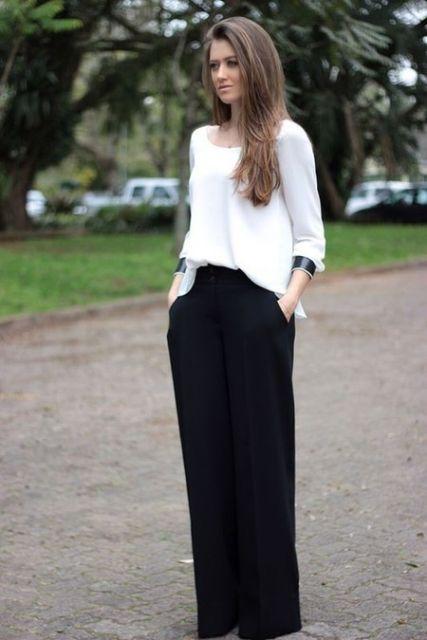 Modelo veste calça preta pantalona e blusa branca modelo mais largo.