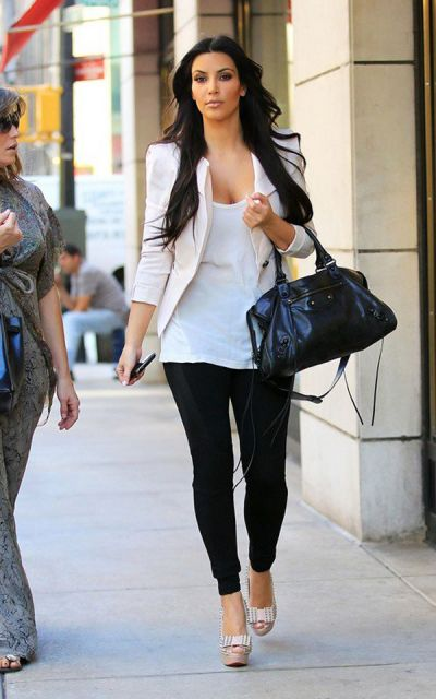 Kim Kadarshian usa calça legging, blusa branca, blazer e sapato nude.