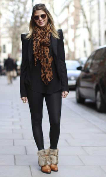 Modelo veste cachecol com estampa onçinha, legging, blusa e blazer preto e botinha vermelho terra de pelinhos.