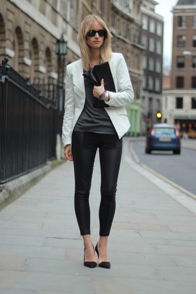 Modelo usa calça montaria, sapato preto bico fino, blusa cinza e blazer branco.