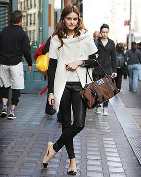 Modelo usa calça montaria preta, casaco com recortes e sapatilha.