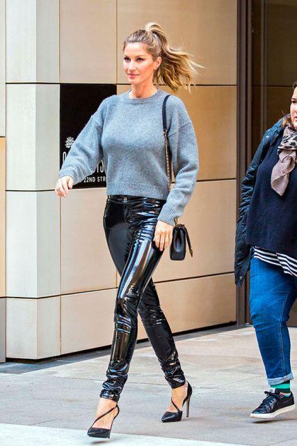 Modelo veste calça preta brilho cintilante , sapato preto e blusa de lão cinza.
