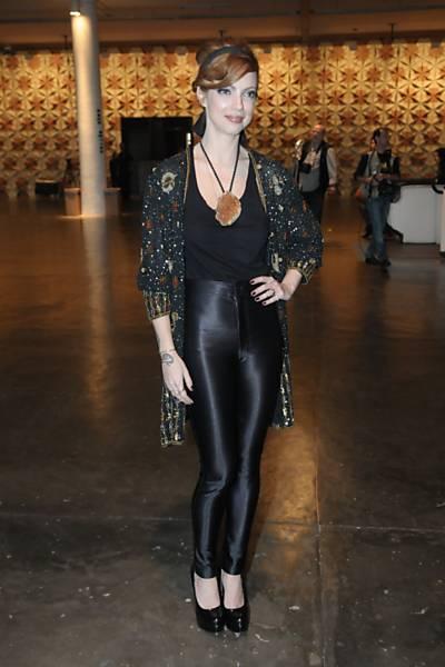 Julia Petit usa calça brilhosa, blusa preta e sobreposição, com colar estiloso.