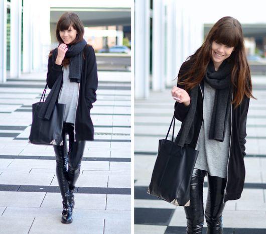 modelo usa casaco preto, blusa cinza, calça preta brilhosa e bolsa de couro.