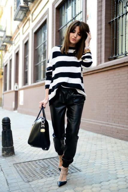 Modelo usa calça preta larguinha brilhosa, blusa listrada em preto e branco e sapato preto.