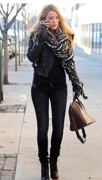Blake lively usa calça jeans preta desbotada com bota preta e casaco no mesmo tom.