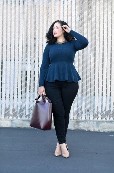 Modelo veste calça jeans preta, com blusa peplum azul manga longa e sapato nude com bolsa em tom meio avermelhado.