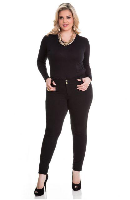 Modelo usa calça, blusa e sapato preto.