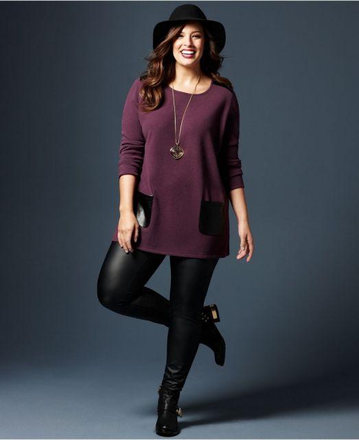 Modelo usa blusa mais compridinha vermelho vinho com detalhes de bolso, calça em couro e botinha preta.