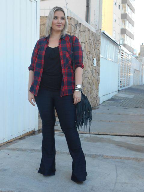 Modelo usa calça flare, blusa preta, sobreposição xadrez e bolsa de franjas azul.