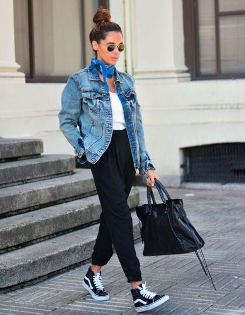 Modelo usa calça cintura alta preta, blusa branca e jaqueta jeans azul.