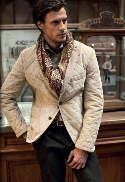 Modelo veste blazer em tom bege claro, calça escura com cinto e echarpe estampada em tom bege .