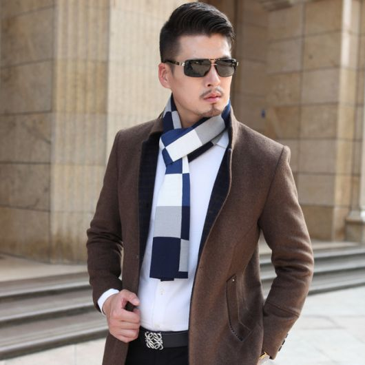 Modelo usa camisa azul, blazer marrom, echarpe mescla de cinza, branco e azul com oculos escuros.