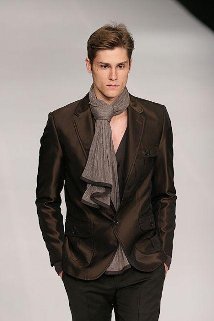 Modelo veste blazer marrom, camisa com gola em V e echarpe cinza chumbo.