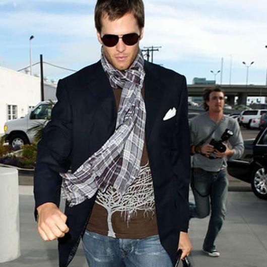 Tom Brady veste blazer preto, camisa estampada marrom, calça jeans e echarpe estampada nos tons de cinza forte e fraco.
