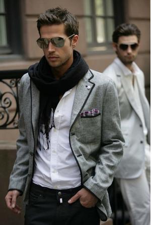 Modelo usa camisa branca, blazer cinza com detalhe em preto, echarpe preta e calça escura.