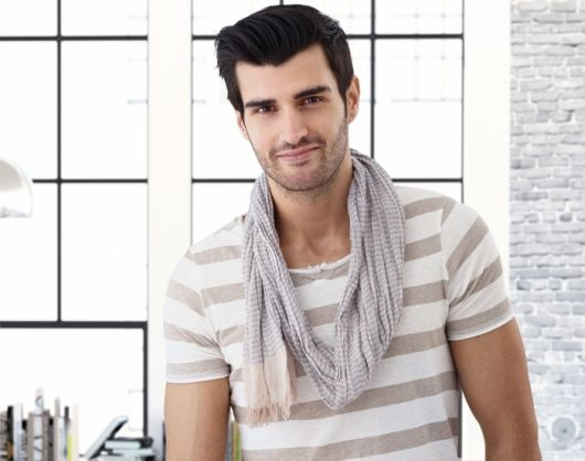 Modelo veste camiseta listrada em branco e tom nude com echarpe cinza claro.
