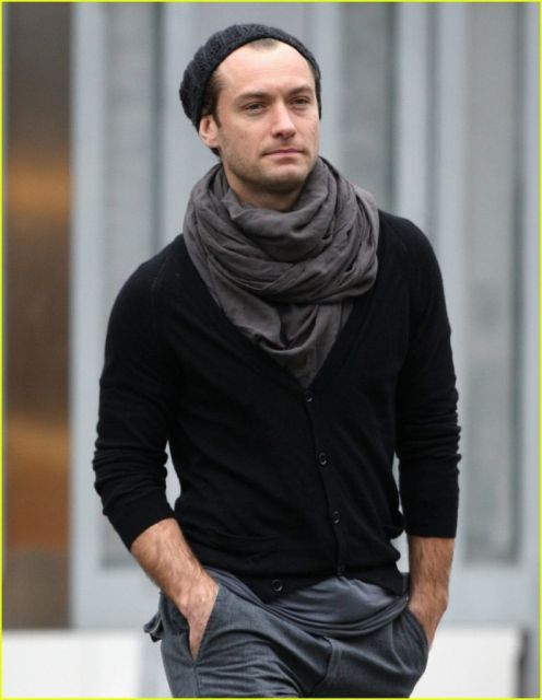 Modelo veste blusa preta manga longa com echarpe cinza.